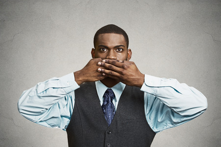 Closeup portrait, silent young business man covering closed mouth observing. Speak no evil concept, isolated black background. Negative human emotion, facial expression sign symbol. Media news coverup photo