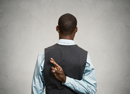 crossing fingers: Closeup young businessman crossing fingers behind his back. Conceptual image business man with his fingers crossed, isolated black background. Human life perception, sign symbol body language reaction Stock Photo