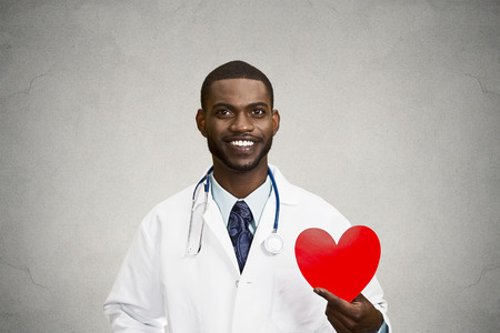 Closeup portrait happy, smiling male health care professional, man family doctor, cardiologist with stethoscope holding red heart, isolated black, grey background. Patient plan, cardiovascular system photo