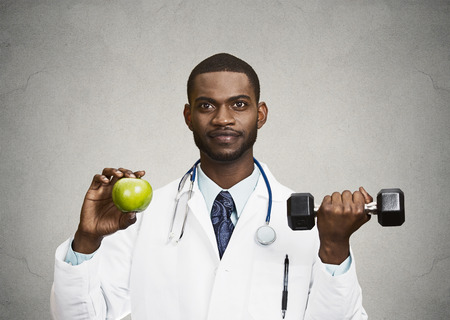 nutrition doctor: Closeup portrait happy, smiling male health care professional, doctor in lab coat holding, lifting green apple, dumbbell, promoting, advising on healthy life style, isolated grey, black background