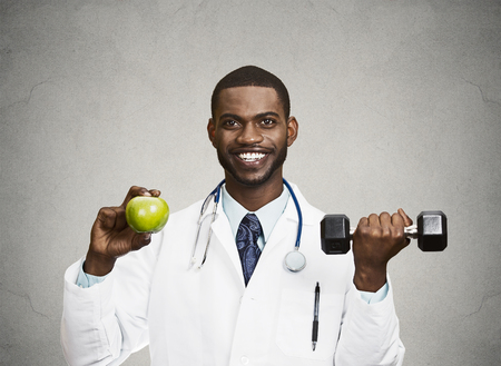 Closeup portrait happy, smiling male health care professional, doctor in lab coat holding, lifting green apple, dumbbell, promoting, advising on healthy life style, isolated grey, black background photo