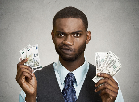 Closeup portrait confused, business man standing, holding dollar and euro bills in hands, isolated grey, black background. Banking exchange rate concept. Facial expression, reaction, body language photo
