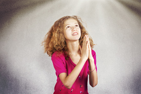 Closeup portrait young girl praying, eyes opened, looking up, hoping for best, asking  forgiveness, miracle, help isolated sky light background. Positive human emotions, facial expressions, feelings photo