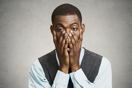 Closeup portrait, headshot young tired, fatigued business man worried, stressed, dragging face down with hands, isolated black, grey background. Negative human emotions, facial expressions, feelings