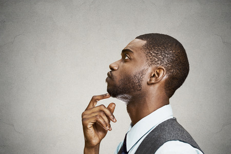 Closeup side view profile portrait, headshot young man daydreaming deeply about something with chin on hand looking upwards, isolated black background space to left. Emotion facial expressions feeling photo