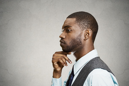 Closeup side view profile portrait, headshot young man daydreaming deeply about something with chin on hand looking down, isolated black background photo
