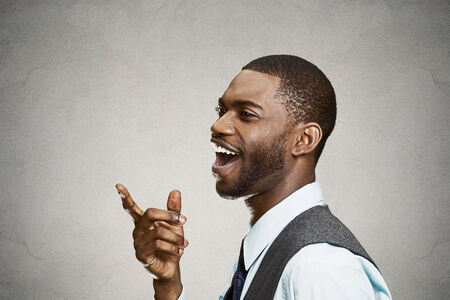 face side: Closeup side view portrait, headshot young man, laughing, pointing with finger at someone, something, isolated black background. Positive human face expression, emotions, feelings, attitude, approach Stock Photo