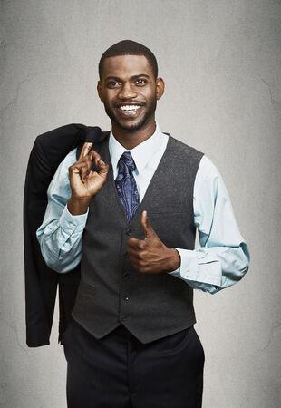 predicador: Primer retrato feliz, sonriente, hombre de negocios atractivo en el juego que da los pulgares para arriba aislados negro fondo gris.