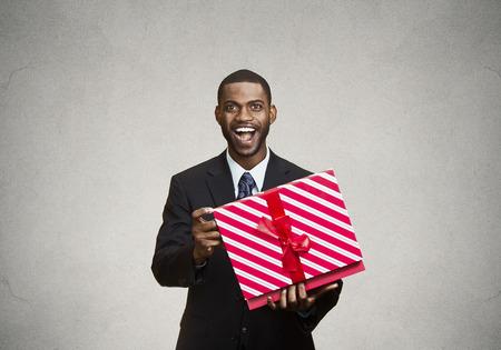 receptivo: Primer retrato de joven feliz hombre emocionado de abrir la caja de regalo de color rojo, complacido, agradecido con lo que recibi�, aislado negro, fondo gris. Foto de archivo