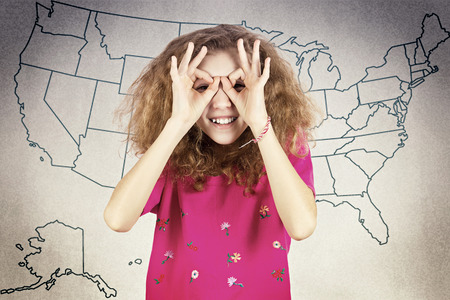 Closeup portrait young pretty happy girl peeking through her fingers like binoculars, searching for something, looking to future at the camera isolated background usa map. Face expression. Sign symbol photo