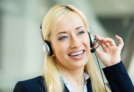 latinamerican: Closeup portrait young happy successful business woman, customer service representative, call centre worker, operator, support staff speaking with head set isolated background corporate office windows