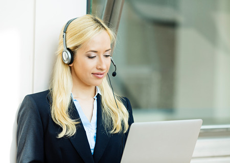 head set: Closeup portrait young happy successful business woman, customer service representative, call centre worker, operator, support staff speaking with head set isolated background corporate office windows