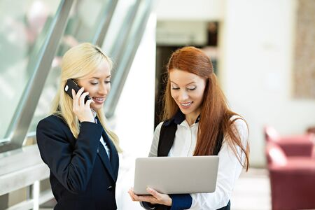 Closeup portrait happy surprised business women, company partners receiving news on computer internet, talking on smart phone celebrating success isolated background corporate office photo