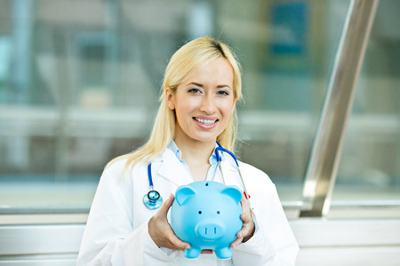 doctor with money: Closeup portrait happy female health care professional, doctor, nurse with stethoscope holding piggy bank Stock Photo