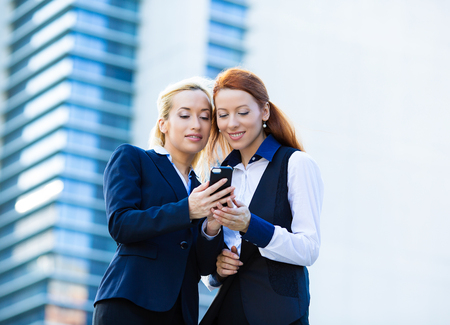 conference call: Closeup portrait happy, attractive businesswomen, corporate employee partners, lawyers looking at smart phone, reading news text message on mobile device isolated background company office building. Stock Photo