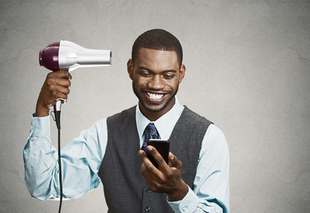 good deal: Closeup portrait happy, smiling business man, deal maker reading good news on smart, mobile phone, holding hairdryer isolated black grey background. Human face expression, emotion, corporate executive