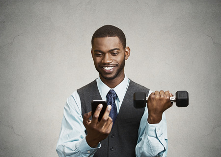simultaneous: Closeup portrait happy, smiling business man reading good news on smart phone, holding mobile, lifting weight, dumbbell isolated black background. Human face expression, emotion, corporate executive