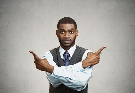 confundido: Retrato del primer confundido joven hombre de negocios que apunta en dos direcciones diferentes, que manera no estoy seguro de ir la vida, reacio a tomar la decisi�n aislar fondo negro. Emoci�n, sentimiento expresi�n facial