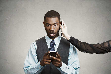 smartphone addiction: Closeup portrait shocked surprised businessman reading bad news on smart cell phone simultaneously listening someone on second mobile isolated black background. Human face expression emotion executive Stock Photo
