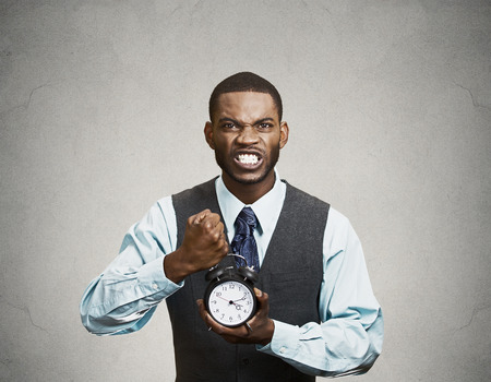 project deadline: Closeup portrait angry, mad, demanding, boss business man, funny looking guy holding alarm clock, screaming, requesting employees to be on time, pushing for project deadline isolated black background