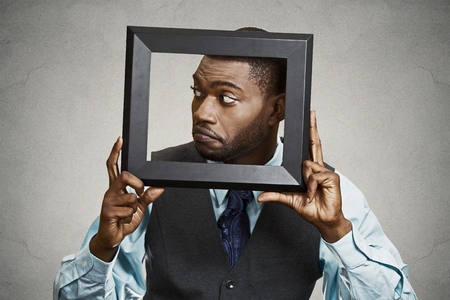mistrust: Closeup portrait businessman executive looking sideways, curious surprised confused through black picture frame thinking beyond borders accepted rules isolated grey background. Face expression emotion