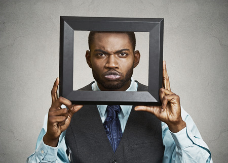 skeptical: Closeup portrait businessman executive looking curious surprised confused skeptical through black picture frame thinking beyond borders accepted rules isolated grey background. Face expression emotion Stock Photo