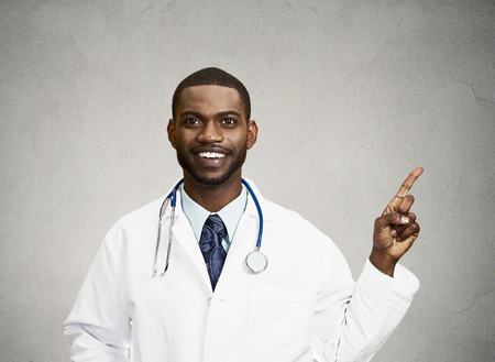 reimbursement: Closeup portrait smiling, happy doctor, pharmacist, dentist pointing with finger at copy space ready for advertisement isolated black background. Positive face expression, emotions, feeling, attitude