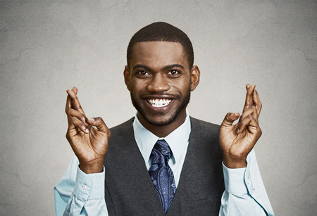 Closeup portrait young funny guy, business man crossing fingers, wishing, hoping for best, miracle isolated black, grey background. Positive human emotions, facial expressions, feelings, attitude Stock Photo
