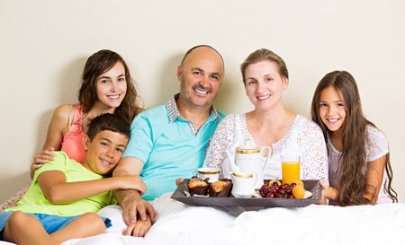 Group portrait happy, smiling, joyful family, mother, father, daughters, son having breakfast in bed, surprise on mom day. Positive human emotions, face expressions, feelings, life perception photo