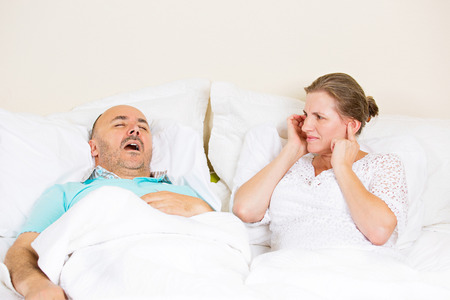apnea: Snoring man. Couple in bed, man snoring and woman can not sleep, covering ears with hands for snore noise. Middle aged couple, attractive woman, caucasian man sleeping in bed at home. Face expressions