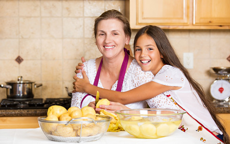 Group portrait of happy, smiling mother and daughter cooking dinner, preparing food isolated background home kitchen. Positive family emotions, face expression, life perception. Healthy eating concept Banque d'images