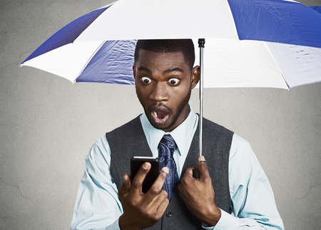 financial service: Closeup portrait shocked, surprised business man, corporate executive reading bad, breaking news on smart phone holding umbrella protected from rain isolated black background  Stock Photo