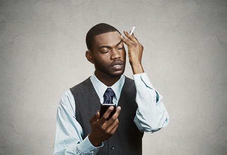 Closeup portrait, headshot mad pissed off business man, corporate executive holding smart phone irritated upset about situation isolated black background  Negative emotion, facial expression reaction photo
