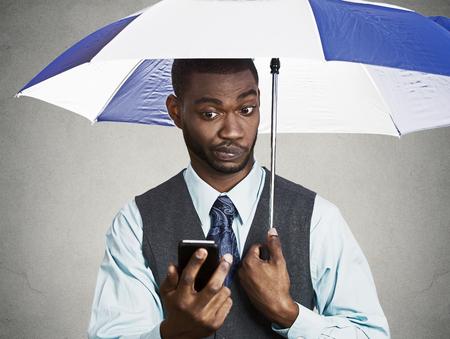 business skeptical: Retrato del primer esc�ptico confundido hombre de negocios corporativos de leer las �ltimas noticias en el tel�fono inteligente que sostiene el paraguas los d�as de lluvia, protegido de la lluvia aisl� el fondo negro Rostro humano emoci�n expresi�n