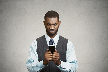 Closeup portrait shocked, displeased, angry, young company businessman unhappy by what he sees on cell phone, isolated black background  Negative human emotion facial expression feeling  Breaking news photo