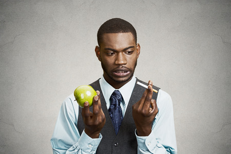 cravings: Closeup portrait headshot corporate executive businessman trying decide on healthy life choices, holding craving cigarette versus green apple isolated black background. Face expression body language Stock Photo