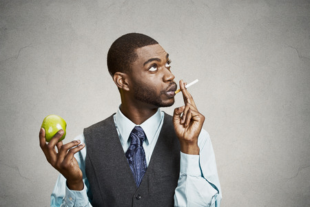 bad apple: Closeup portrait headshot corporate executive businessman making bad health choices, smoking cigarette instead of having fresh green apple isolated black background. Face expressions, body language Stock Photo