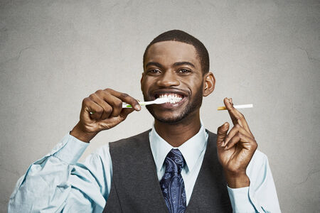 Closeup portrait, headshot  young business man, company, corporate executive holding toothbrush, cigarette, isolated black background. Smoker breath concept. Face expression, perception. Oral hygiene photo