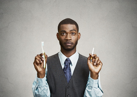oral hygiene: Closeup portrait, headshot  young business man, company, corporate executive holding toothbrush, cigarette, isolated black background. Smoker breath concept. Face expression, perception. Oral hygiene