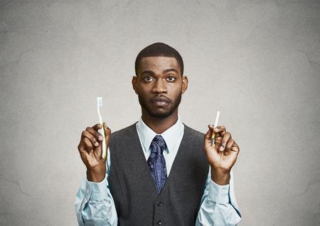 higiene bucal: Primer retrato, headshot joven hombre de negocios, empresa, ejecutivo de una empresa que sostiene el cepillo de dientes, cigarrillos, fondo negro aislado. Concepto aliento Fumador. Cara de la expresión, la percepción. La higiene bucal