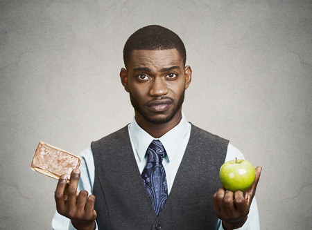 weight control: Closeup portrait headshot corporate executive, businessman trying to decide on diet, sweet cookie versus green fresh apple isolated black grey background. Weight control eating habits. Face expression Stock Photo