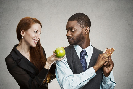 disease control: Closeup portrait young nutritionist woman trying to convince stubborn man to eat healthy apple fruit instead of sweet cookie, isolated black background. Negative emotions, facial expressions, feeling