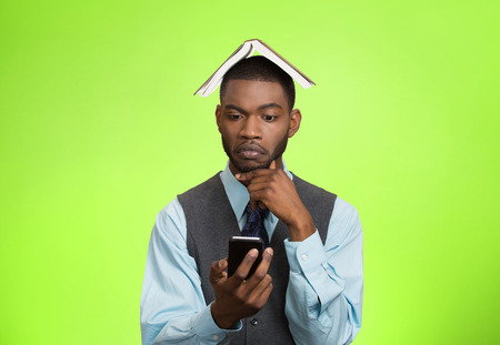 simultaneous: Closeup portrait business man corporate executive thinking how to reply to message on smart phone holding mobile, book over head isolated green background.