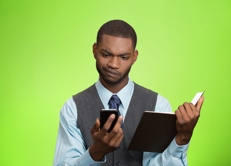 business skeptical: Closeup portrait confused, skeptical business man, executive reading news on smart phone, holding book isolated green background. Stock Photo