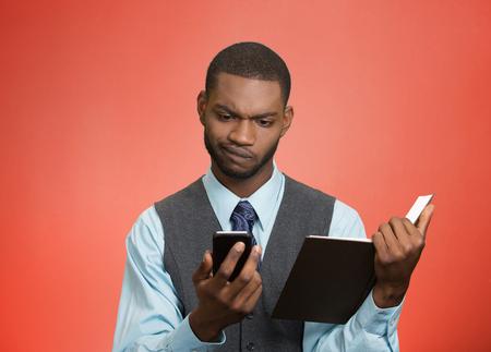business skeptical: Retrato del primer confundido, el hombre de negocios esc�ptico, noticias ejecutivo lectura en el tel�fono inteligente, que sostiene el libro aislado fondo rojo. La expresi�n humana cara, emoci�n, el lenguaje corporal, el estilo de vida corporativa