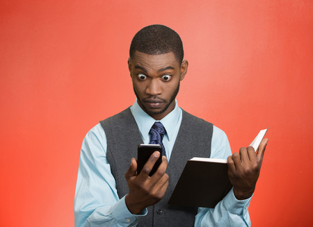 shocked face: Closeup portrait surprised shocked business man executive reading breaking news on smart phone holding book isolated red background. Human face expression, emotion, corporate company lifestyle