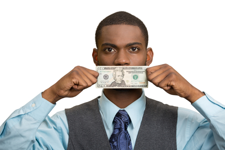 no integrity: Closeup portrait handsome young corrupt corporate man in blue shirt holding twenty dollar bill to mouth, isolated white background. Bribery concept in politics, business, diplomacy. Life perception