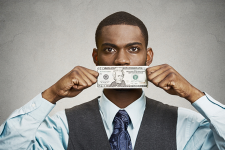 no integrity: Closeup portrait handsome young corrupt corporate man in blue shirt holding twenty dollar bill to mouth, isolated grey background. Bribery concept in politics, business, diplomacy. Life perception Stock Photo