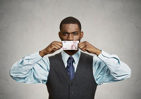 sweeten: Closeup portrait handsome young corrupt corporate man in blue shirt holding euro bill currency to his mouth, isolated grey background. Bribery concept in politics, business, diplomacy. Life perception Stock Photo