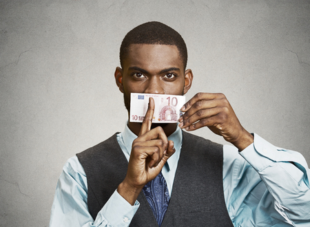 Closeup portrait handsome corrupt guy, businessman holding euro bill currency to mouth, showing shhh sign, isolated grey background. Bribery concept in politics, business, diplomacy. Face expressions Stock Photo